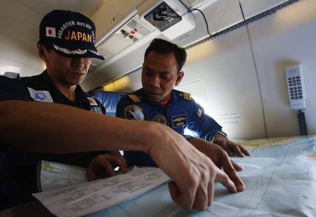 Japan Coast Guard (JCG) Captain Tojo Hideo (L) studies a map with Malaysia Maritime Enforcement Agency's Captain Sharen as they take off in JCG's Gulfstream V Jet aircraft customized for search and rescue operations as they search for the missing Malaysia Airlines MH370 plane over the waters of the South China Sea March 15, 2014. REUTERS/Edgar Su