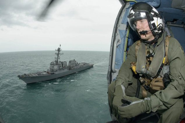 Naval Aircrewman 2nd Class Cody Witherspoon, assigned to Helicopter Maritime Strike Squadron (HSM) 35, keeps a lookout as his helicopter returns to the guided-missile destroyer USS Sampson (DDG 102). Sampson is supporting Indonesian-led search efforts to locate Air Asia Flight QZ8501, January 6, 2015. U.S. Navy photo
