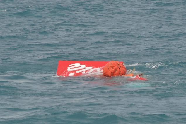 Part of the tail of AirAsia QZ8501 floats on the surface after being lifted as Indonesian navy divers. REUTERS/Adek Berry/Pool