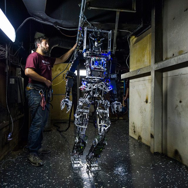 MOBILE, Ala. (Nov. 6, 2014) John Seminatore, a graduate student at Virginia Tech, secures the Office of Naval Research-sponsored Shipboard Autonomous Firefighting Robot (SAFFiR) during testing aboard the Naval Research Laboratory's ex-USS Shadwell in Mobile, Alabama. The bipedal humanoid robot, developed as a test bed for autonomous firefighting and damage control operations, was tethered to a power source for demonstrations aboard the NavyÕs fire test platform. (U.S. Navy photo by John F. Williams/Released)