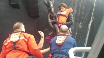 Crew members from Coast Guard Station Bellingham, Wash., assist Chiara D'Angelo, an activist, down from the anchor chain of Arctic Challenger in the Port of Bellingham, May 25, 2015. D'Angelo was taken back to Station Bellingham, where she was evaluated by EMS and released. (U.S. Coast Guard photo courtesy of Station Bellingham)