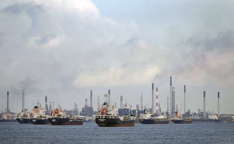 Ships are seen anchored in front of a refinery on Singapore's Bukom Island in this July 6, 2014 file photo. REUTERS/Tim Wimborne/Files