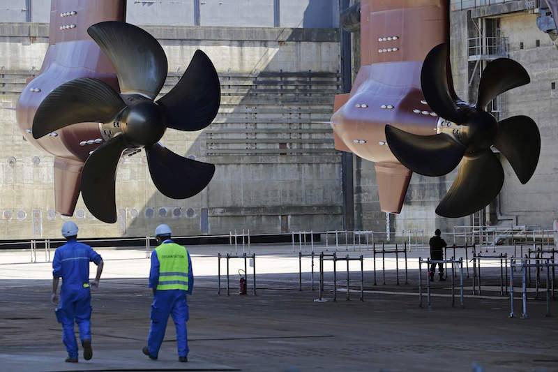 Ship builders walk near propellers of the Harmony of the Seas ( Oasis 3 ) class ship at the STX Les Chantiers de l'Atlantique shipyard site in Saint-Nazaire, France, June 17, 2015. REUTERS/Stephane Mahe