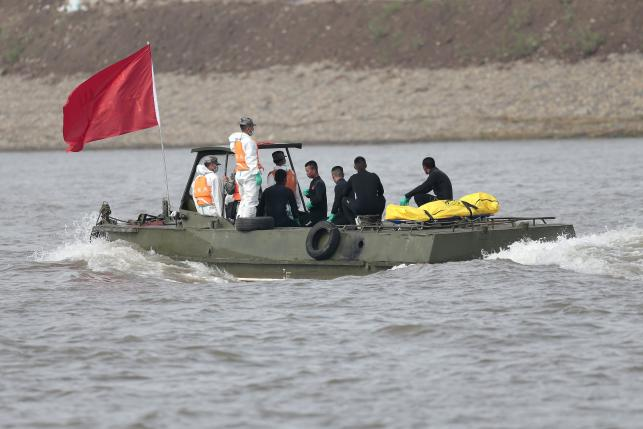 Rescue workers transport body near site where cruise ship Eastern Star capsized during a media trip to site of the sinking, organised by Chinese government, in Jianli section of Yangtze River, Hubei province