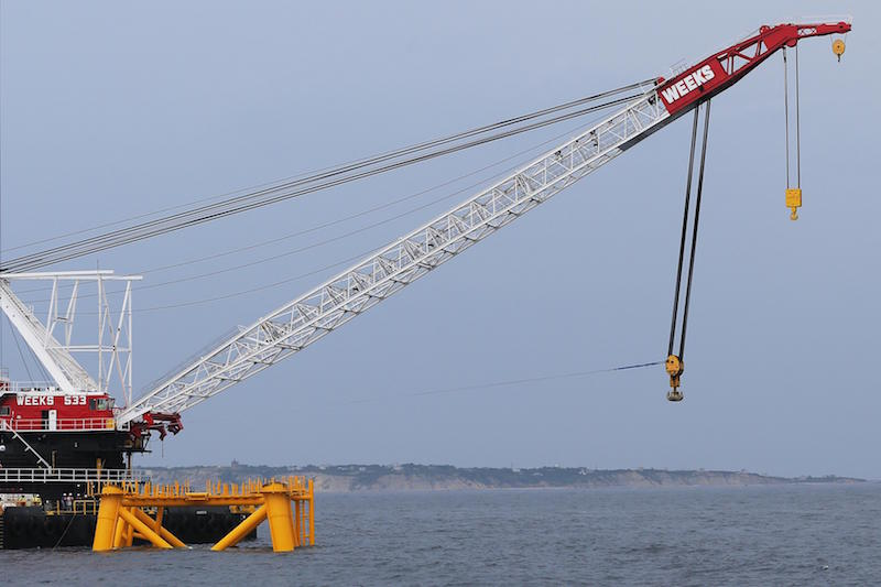 A crane hangs over the first jacket structure installed to support a turbine for a wind farm in the waters of the Atlantic Ocean off Block Island (rear), Rhode Island July 27, 2015.      REUTERS/Brian Snyder