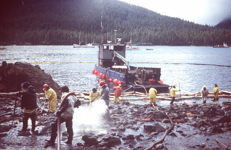 Cleanup workers steam blast rocks and washdown shorelines soaked in crude oil from the leaking tanker Exxon Valdez. The Exxon Valdez ran aground on Bligh Reef in Prince William Sound, Alaska, March 23, 1989 spilling 11 million gallons of crude oil, which resulted in the largest oil spill in U.S. history. U.S. Coast Guard Photo