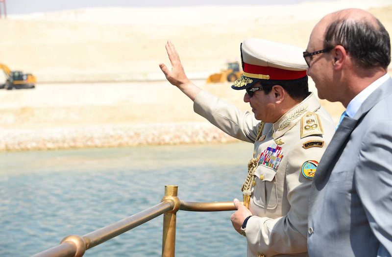 Egyptian President Abdel Fattah al-Sisi (L) and Mohab Mameesh, chairman of the Suez Canal Authority, stand in a boat inside the Suez Canal as they attend the celebration, August 6, 2015. REUTERS/The Egyptian Presidency/Handout