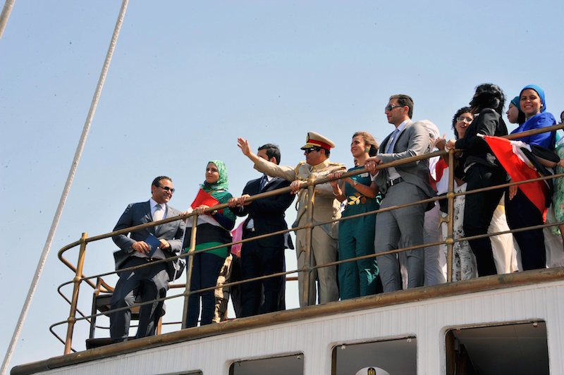 Egyptian President Abdel Fattah al-Sisi waves from a boat on the Suez Canal, August 6, 2015. REUTERS/The Egyptian Presidency/Handout