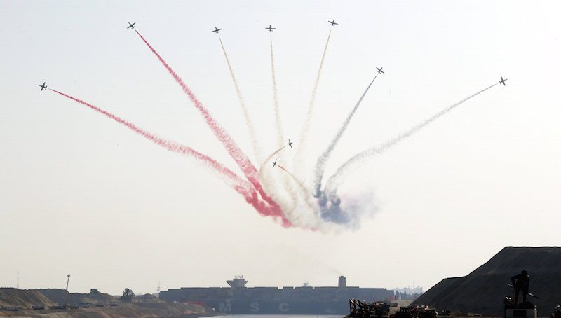 Egyptian air force planes parade in front of cargo container ship crossing new section of the Suez Canal after the opening ceremony of the new Suez Canal, in Ismailia