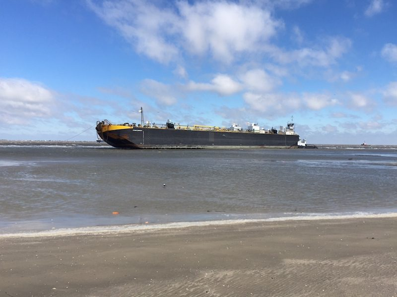 The tugboat, Peter F Gellatly and barge, Double Skin 504, sit grounded near East Beach after high winds pushed it from Bolivar Roads Anchorage, Sunday, Oct. 25, 2015. U.S. Coast Guard Photo