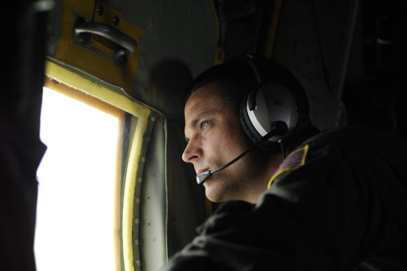 Petty Officer 3rd Class Jimmy Feenstra, an Aviation Machinery Technician from Air Station Elizabeth City, looks through the window of a C-130 aircraft, July 25, 2013, during a training flight. U.S. Coast Guard photo by Petty Officer 3rd Class David Weydert