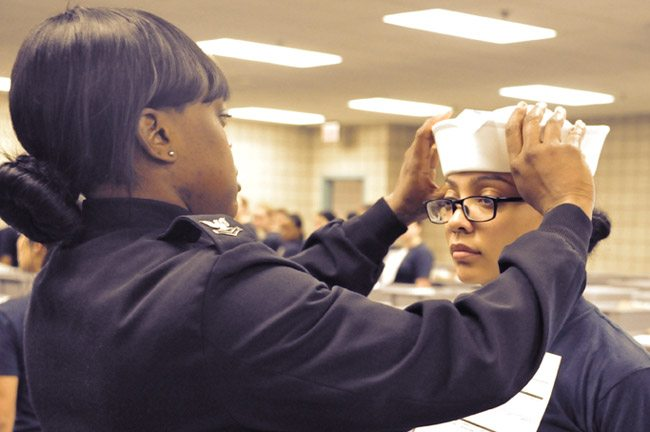 "160404-N-CM124-002 GREAT LAKES, Ill. (April 4, 2016) Engineman 2nd Class Shanice Floyd, a recruit division commander, ensures the proper fit of Seaman Recruit Megan Marte's white enlisted hat, or ""Dixie cup,"" during uniform issue at Recruit Training Command. Marte was among the first female recruits to be issued the Dixie cup as part of the Navy's efforts for uniformity in service members' uniforms. (U.S. Navy photo by Sue Krawczyk/Released)"