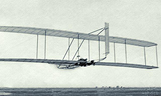 Wilbur Wright gliding, Kitty Hawk Lifesaving Station and Weather Bureau in distance; Kitty Hawk, North Carolina, 1902.