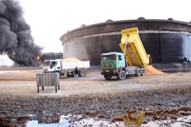 File photo of smoke rising from burning oil storage tanks in the port of Ras Lanuf, Libya