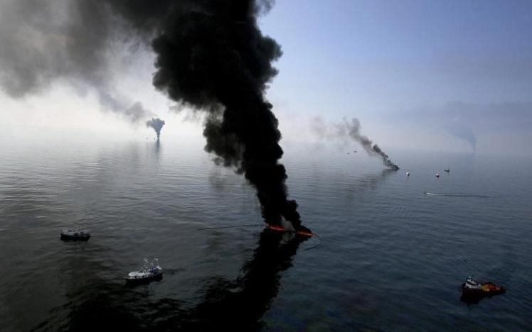 Smoke billows from a controlled burn of spilled oil off the Louisiana coast in the Gulf of Mexico coast line