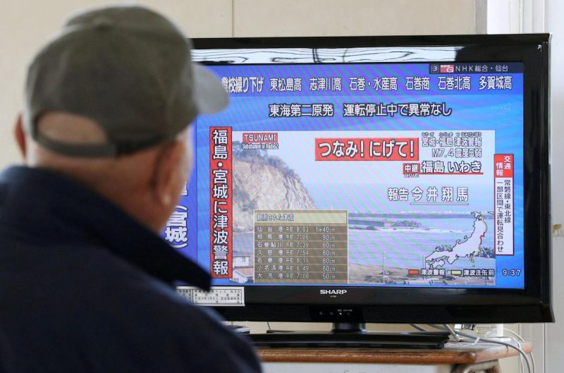 A man evacuated from his home looks at a television screen showing a news report on tsunami warnings, at a shelter following an earthquake, in Sendai, Japan, in this photo taken by Kyodo November 22, 2016. Mandatory credit Kyodo Kyodo/via REUTERS