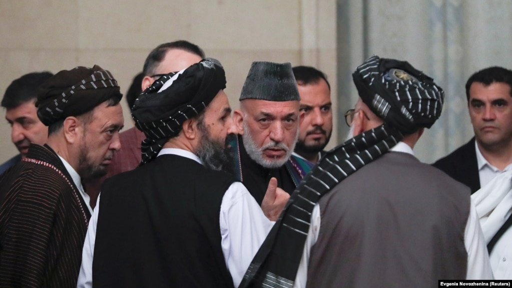 FILE: Former Afghan President Hamid Karzai (2nd R) and cheif Taliban negotiator Mullah Abdul Ghani Baradar (3rd R) talk in Moscow.