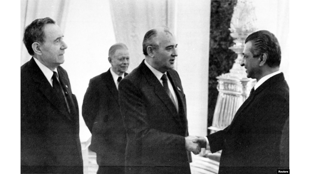 Karmal shakes hands with Soviet leader Mikhail Gorbachev (center) on a visit to Moscow in 1985.
