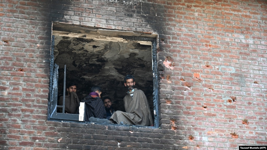 Kashmiri villagers look inside a damaged house following a gunfight between militants and Indian government forces at Panjran village in Pulwama, south of Srinagar on June 7.