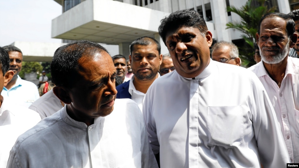 Sajith Premadasa (2nd R) deputy leader and Kabir Hashim (L) senior member of the deposed Prime Minister Ranil Wickremesingehe-led United National Party talk as they leave the Supreme Court after filing a petition against the President Maithripala Sirisena