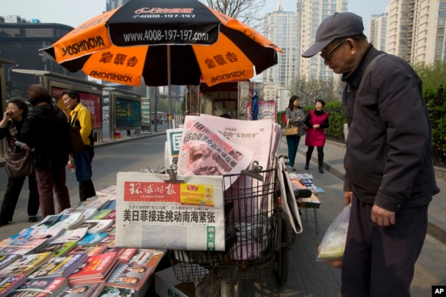 """A man looks at a newsstand with a copy of the day's Global Times displayed on a basket in Beijing, April 5, 2016. The nationalistic tabloid published an editorial saying an unidentified """"powerful force"""" was behind the documents leaked from a Panama-based law firm that name relatives of current and retired Chinese politicians, including President Xi Jinping, as owning offshore companies."""