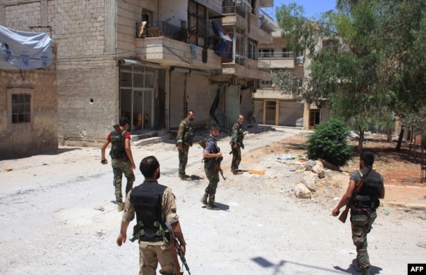FILE - Syrian army soldiers patrol a street in government-controlled Aleppo's al-Khalidiya area where the army progressed toward the industrial zone of al-Layramoun and Bani Zeid, June 28, 2016.