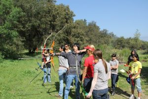 Olympian Khatuna Lorig (in red) runs coaching clinics all over the country for young archers in the Junior Olympic Archery Development (JOAD) program. Photo courtesy of Pasadena Roving Archers.