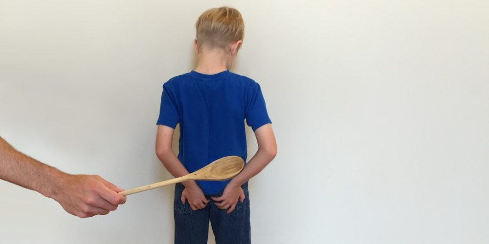 A boy stands facing a wall, hands on his buttocks, while a wooden spoon is held up behind him as if to spank.