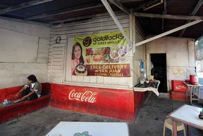 coca-cola-painted-on-store-with-a-woman-on-a-bench