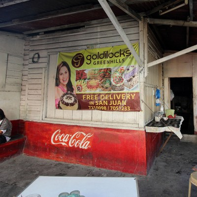 store with Coca Cola sign with a woman on a bench