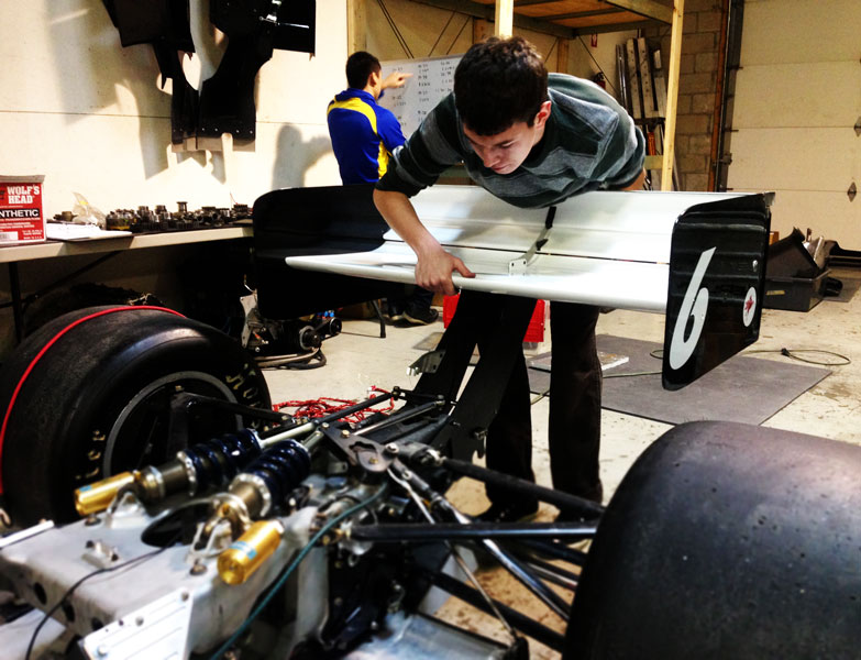 Chris is taking the rear wing off of the 97 Reynard while Lawrence is busy crunching numbers