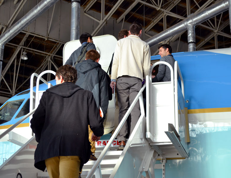 Members of the Genius Garage team crowd around the entrance to an Air Force One plane.
