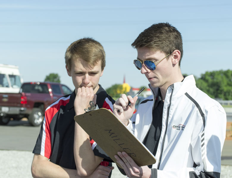 Clint and Dan review and study the checklist while preparing the car for the test day.