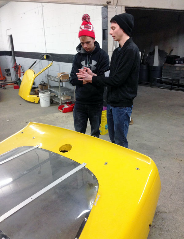 Daniel Miller and Clint Teece discuss possible chassis modifications in their down time.