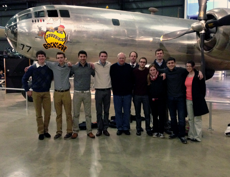 The team gets a picture with team mentor Jim Barfield by the Bockscar plane at the end of their tour.