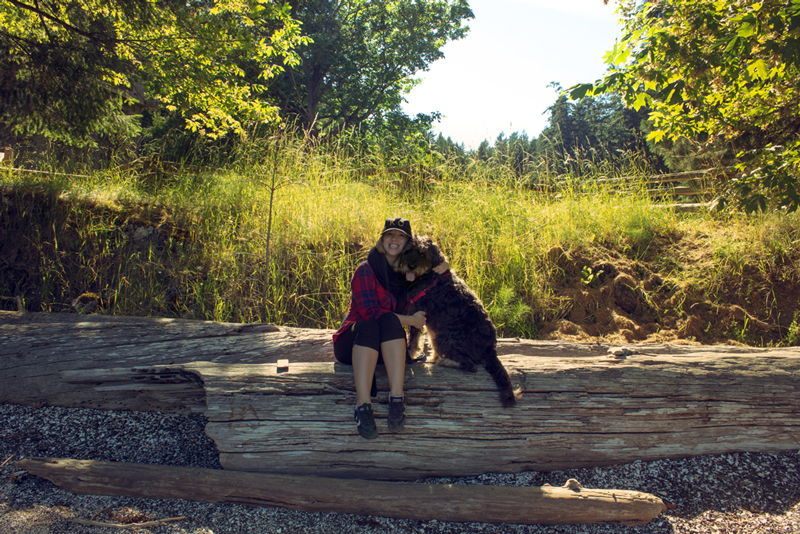 a girl and her dog on a log