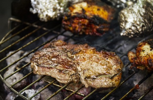 tasty-fresh-appetizing-meat-beef-on-grill-cooking-on-open-fire-on-grill-grid-nature-background-closeup_1220-1378