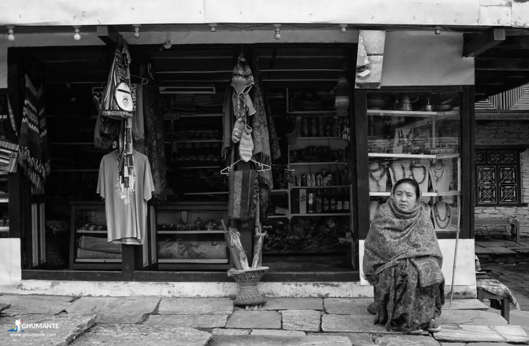 Shopkeeper in front of her shop.
