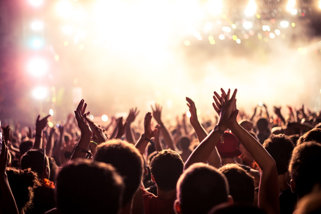 Audience with hands raised at a music festival and lights streaming down from above the stage. Soft focus blurred movement.