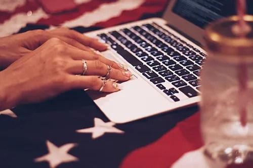 MacBookを操作する女の子のフリー写真素材(商用可)