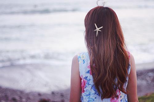 丸太に座って海を眺める女の子のフリー写真素材(商用可)