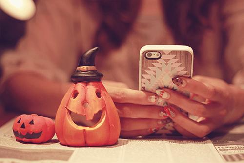スマートフォンからハロウィンパーティーのお知らせをしている女の子のフリー写真素材(商用可)