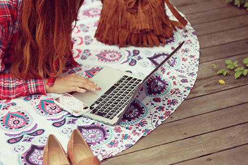 外でパソコンを広げ、青空コーディングをする女の子のフリー写真素材(商用可)