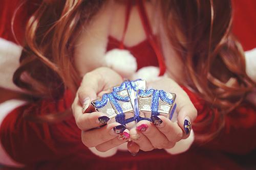 松ぼっくりやリンゴを差し出すサンタクロースな女の子のフリー写真素材(商用可)