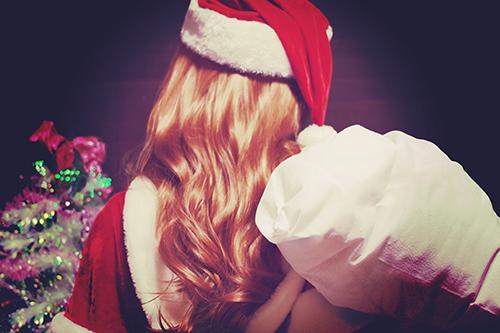 みんなが寝静まった深夜にプレゼントをかついでやってきたサンタクロースの女の子のフリー写真素材(商用可)