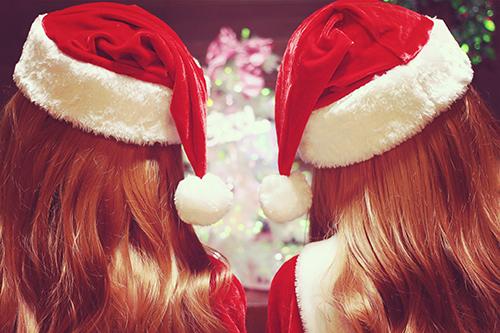 クリスマスパーティでサンタ帽を寄せ合う双子サンタクロースな女の子のフリー写真素材(商用可)