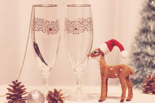 クリスマスリースの向こうでゆらめくキャンドルのフリー写真素材(商用可)