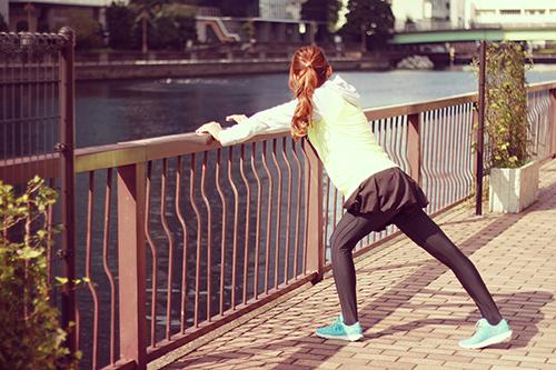 走る前の準備体操をする女の子のフリー写真素材(商用可)