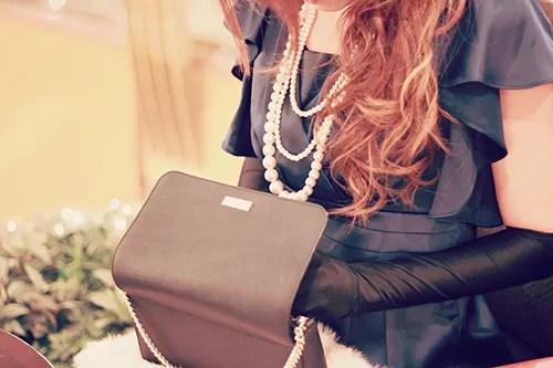 クラッチバッグから何かを取り出しているパーティドレスの女の子のフリー写真素材(商用可)