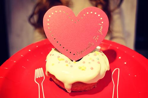 手作りデコドーナツを差し出す女の子のフリー写真素材(商用可)